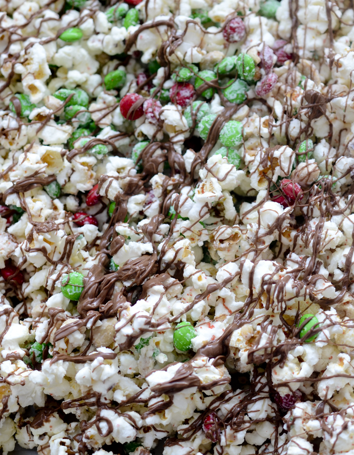 Christmas Crunch Popcorn - Christmas Crunch Popcorn is packed with peanuts, red and green M&M candies, and almond bark. The perfect gift giving snack to bring for someone around the Holidays.