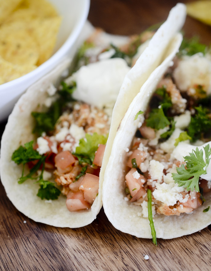 Chicken Tinga Tacos - spicy tacos with marinated chicken, cotija cheese, pico de gallo, and sour cream.
