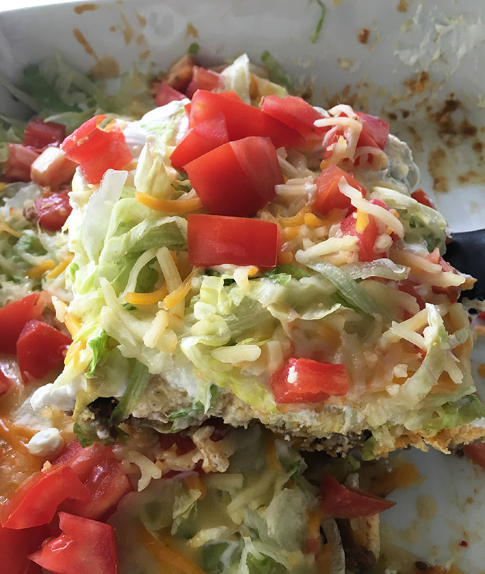 Taco Casserole - this taco casserole is made with layers of taco seasoned ground beef, a layer of baking mix, and taco toppings! Easy to throw together and great for a pot luck or Taco Tuesday.